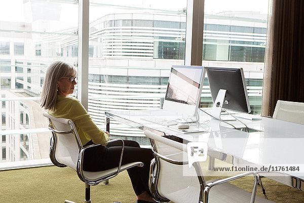 Geschäftsfrau am Schreibtisch im Büro  London  UK Geschäftsfrau am Schreibtisch im Büro, London, UK
