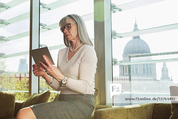 Geschäftsfrau benutzt digitales Tablet auf Bürosofa. London  Vereinigtes Königreich Geschäftsfrau benutzt digitales Tablet auf Bürosofa. London, Vereinigtes Königreich