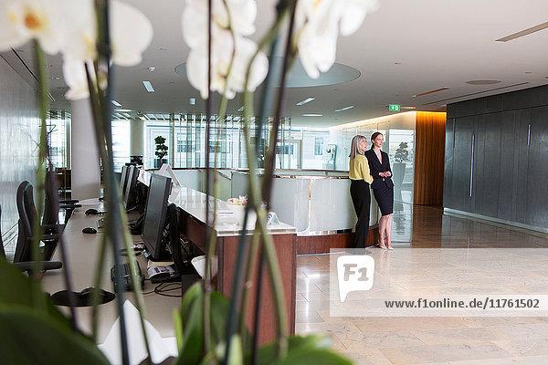 Geschäftsfrauen sprechen im Empfangsbereich des Büros Geschäftsfrauen sprechen im Empfangsbereich des Büros