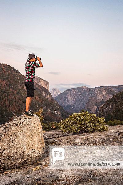 Mann steht auf einem Felsblock und schaut durch ein Fernglas  Yosemite National Park  Kalifornien  USA