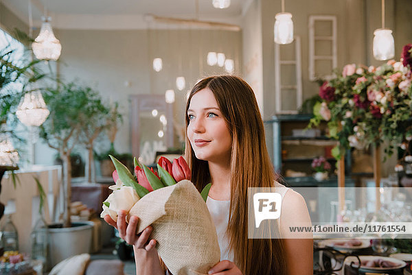 Customer in flower shop  holding bunch of flowers