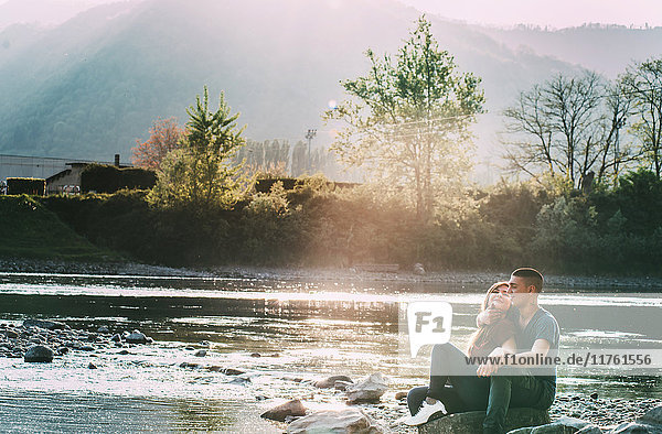 Romantisches Paar sitzt auf Felsen am Fluss und lächelt