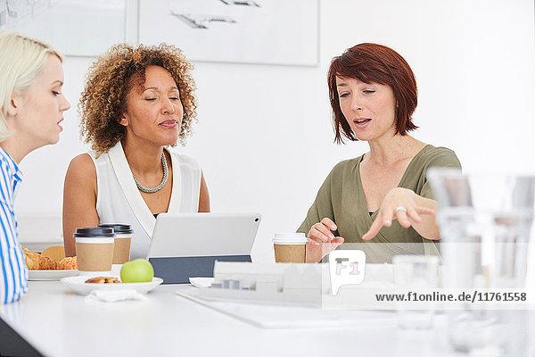 Architektin erklärt in Teambesprechung Architekturmodell auf dem Tisch