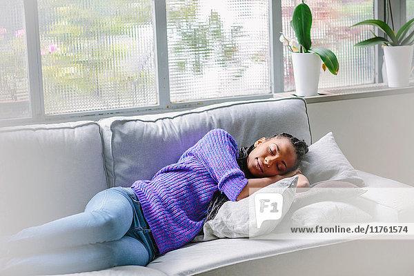Frau schläft auf Sofa
