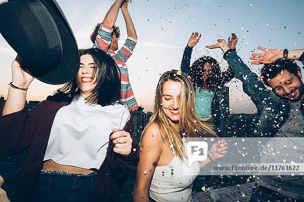 Gruppe von Freunden tanzt  genießt Dachparty  Konfetti in der Luft