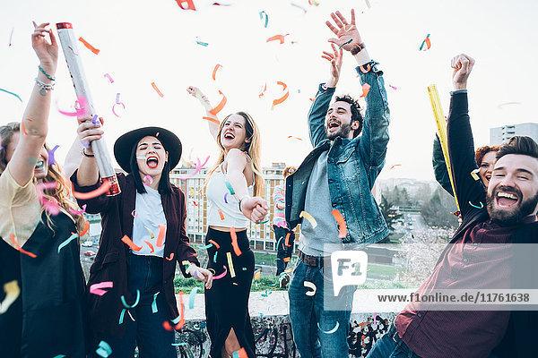 Gruppe von Freunden genießt Dachparty  Konfetti in der Luft
