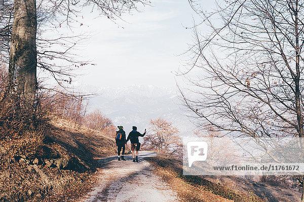 Rückansicht eines Wanderpaares beim Wandern entlang einer Landstraße  Monte San Primo  Italien