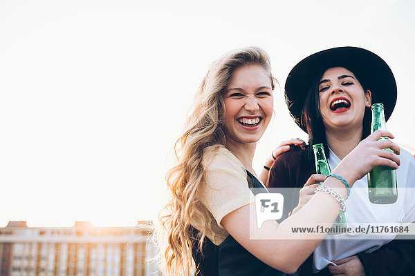 Two young women  outdoors  drinking bottled beer  laughing