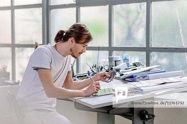 Mann am Zeichenbrett mit digitalem Tablett