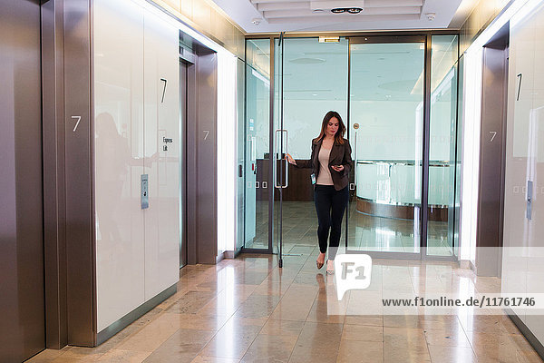 Geschäftsfrau geht durch die Bürotür