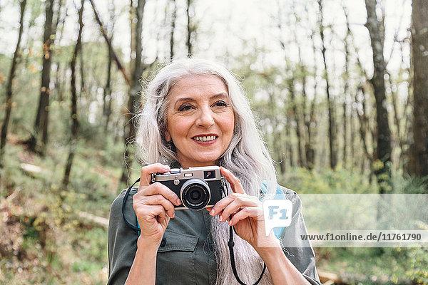 Reife Frau mit langen grauen Haaren beim Fotografieren im Wald  Scandicci  Toskana  Italien
