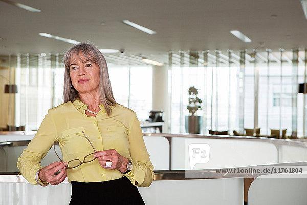 An den Empfang gelehnte Geschäftsfrau An den Empfang gelehnte Geschäftsfrau