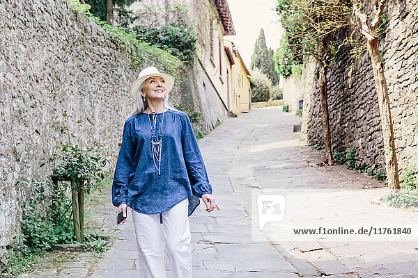 Stilvolle  reife Frau schlendert auf gepflasterter Straße  Fiesole  Toskana  Italien
