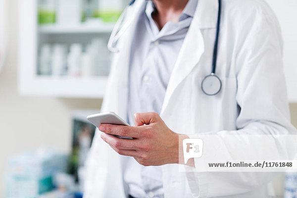 Arzt im Krankenhaus hält Mobiltelefon