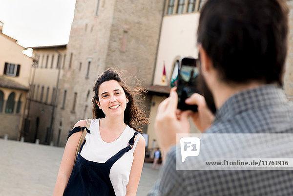 Über-Schulter-Ansicht eines Mannes  der seine Freundin fotografiert  an der Kathedrale von Arezzo  Arezzo  Toskana  Italien