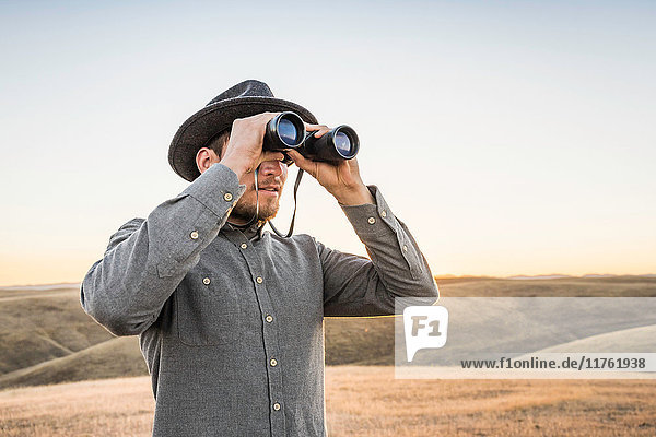 Man looking through binoculars at rolling prairie hills  Bakersfield  California  USA