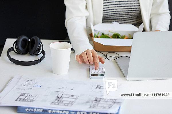 Mittlere Sektion der Designerin beim Drücken der Smartphone-Tastatur am Bürotisch