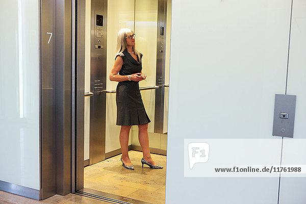 Geschäftsfrau im Bürolift stehend Geschäftsfrau im Bürolift stehend