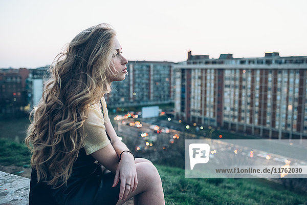 Junge Frau sitzt auf dem Dach  schaut auf die Aussicht  nachdenklicher Ausdruck