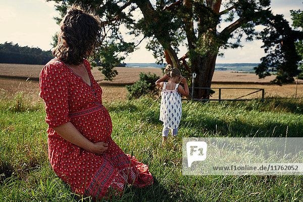 Schwangere Frau sitzt auf dem Feld und beobachtet Kleinkind-Tochter