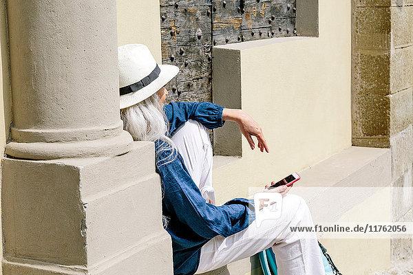 Stilvolle  reife Frau sitzt vor der Kirche  Fiesole  Toskana  Italien