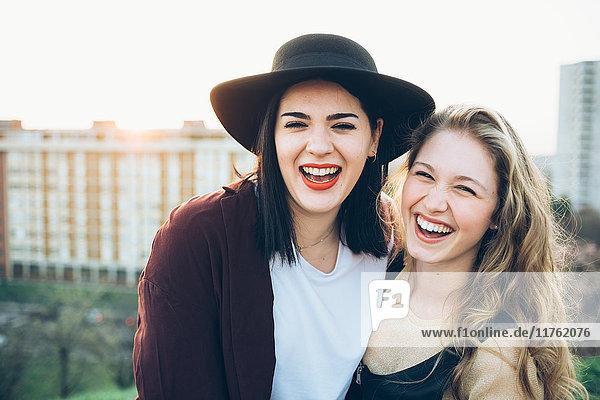 Porträt von zwei jungen Frauen  auf dem Dach  lächelnd