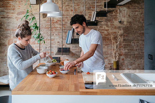 Young couple preparing breakfast at kitchen counter