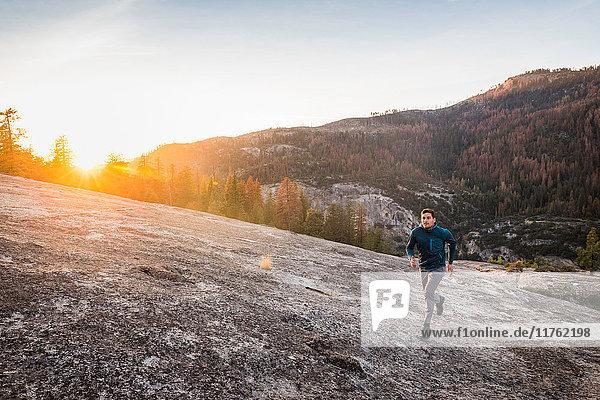 Mann läuft bei Sonnenuntergang auf Felsoberfläche  Yosemite National Park  Kalifornien  USA