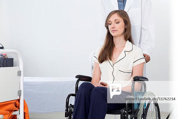 Frau im Schlafanzug im Krankenhaus im Rollstuhl sitzend