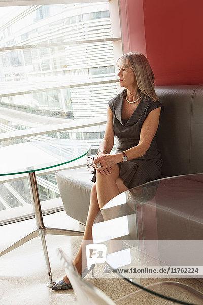 Geschäftsfrau am Bürofenster sitzend  London  UK Geschäftsfrau am Bürofenster sitzend, London, UK