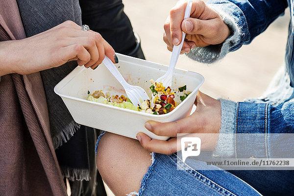 Hände von jungen Frauen  die sich Essen zum Mitnehmen teilen
