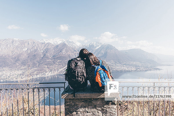 Rear view of couple sitting on terrace wall over mountain lakeside  Monte San Primo  Italy