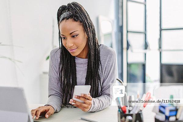 Frau benutzt Computer und Mobiltelefon