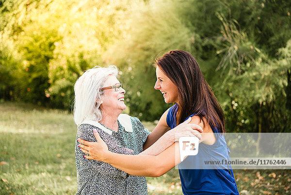 Senior woman  hugging granddaughter  outdoors