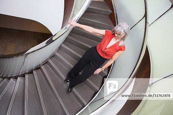 Geschäftsfrau geht eine Wendeltreppe hinunter Geschäftsfrau geht eine Wendeltreppe hinunter