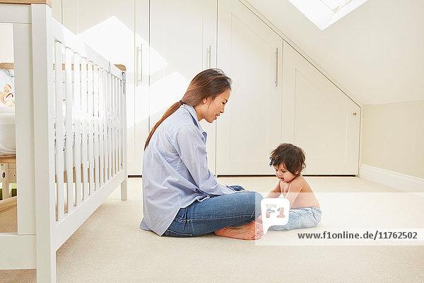 Frau sitzt auf dem Boden und spielt mit ihrer kleinen Tochter