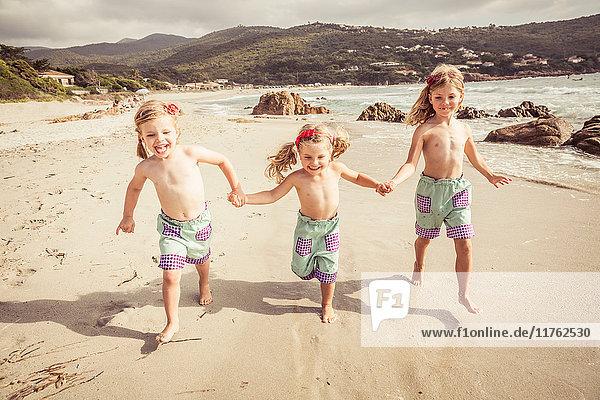 Drei junge Schwestern halten sich an den Händen  laufen am Strand entlang und lächeln