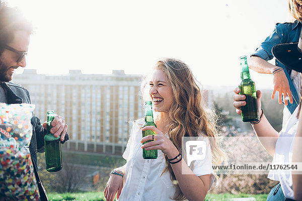 Group of friends holding beer bottles  enjoying roof party