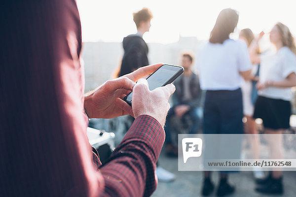 Gruppe von Freunden genießt Dachparty  junger Mann benutzt Smartphone