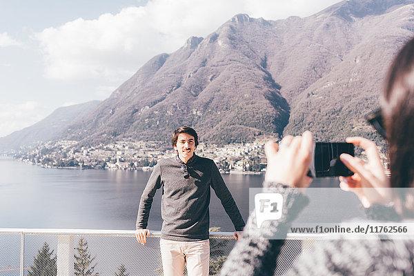 Über-Schulter-Ansicht einer Frau  die ihren Freund am Seeufer fotografiert  Monte San Primo  Italien