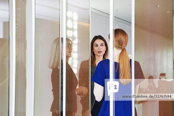 Geschäftsfrauen stehen und diskutieren Geschäftsfrauen stehen und diskutieren