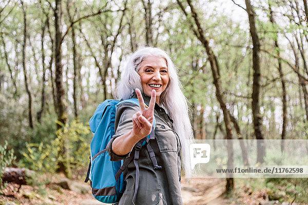 Porträt einer reifen Rucksacktouristin beim Friedenszeichen im Wald  Scandicci  Toskana  Italien