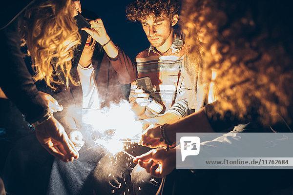 Gruppe von Freunden genießt Dachparty  zündet Wunderkerzen an