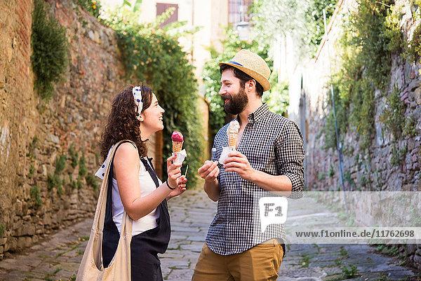 Couple with ice cream cones on cobbled street  Arezzo  Tuscany  Italy