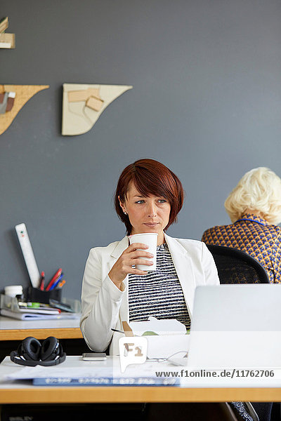 Female designer looking at laptop and drinking coffee at office desk