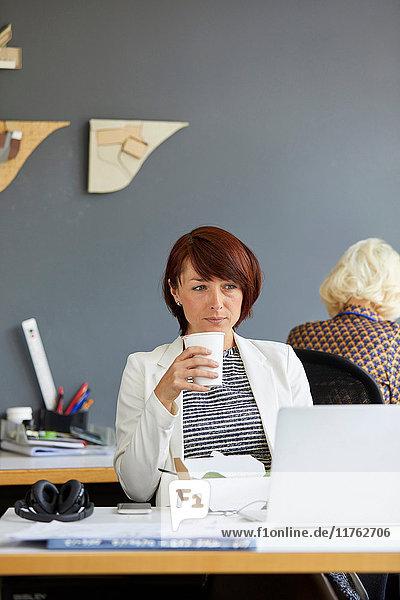 Designerin schaut auf Laptop und trinkt Kaffee am Bürotisch