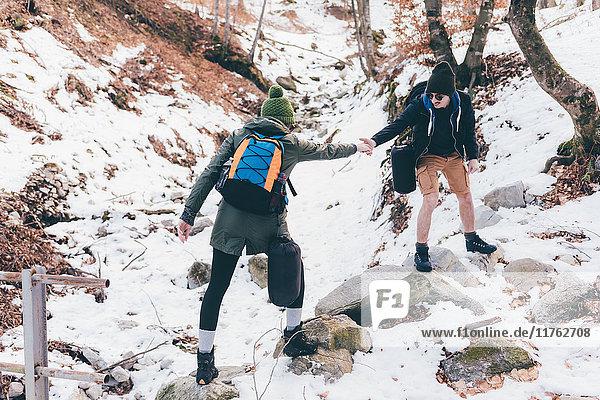 Mann wandert im verschneiten Wald und gibt seiner Freundin eine helfende Hand  Monte San Primo  Italien