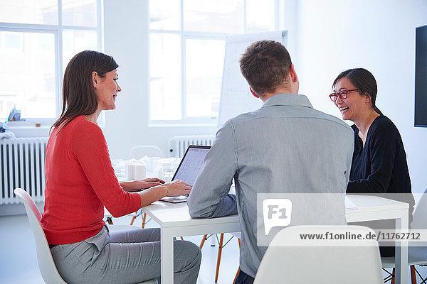 Kollegen mit Laptop im Büro bei einer Besprechung