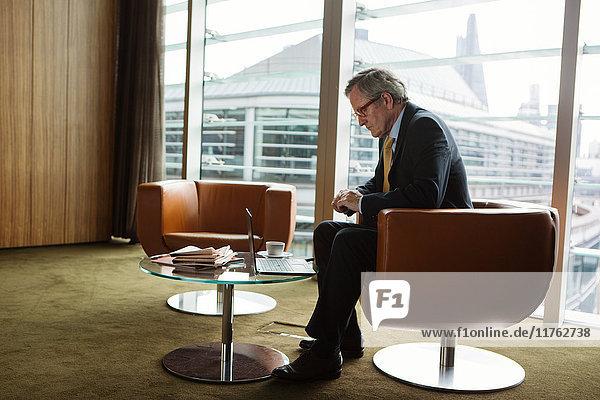 Geschäftsmann mit Laptop im Kaffeebereich im Büro  London  Großbritannien Geschäftsmann mit Laptop im Kaffeebereich im Büro, London, Großbritannien