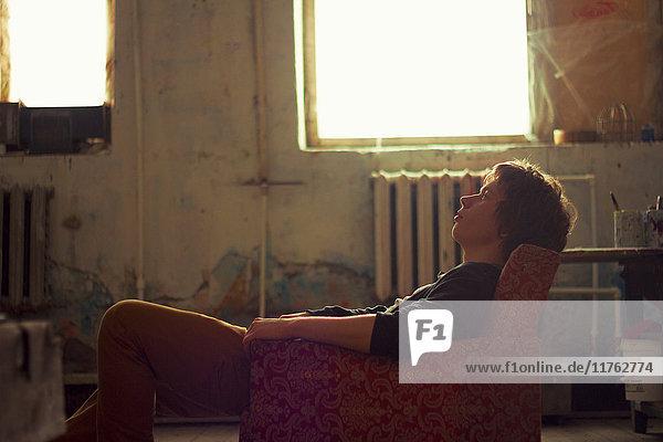 Young man sitting on vintage armchair in artist studio gazing upward